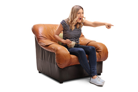 hilarious: Laughing young woman watching something hilarious on TV and having some popcorn isolated on white background