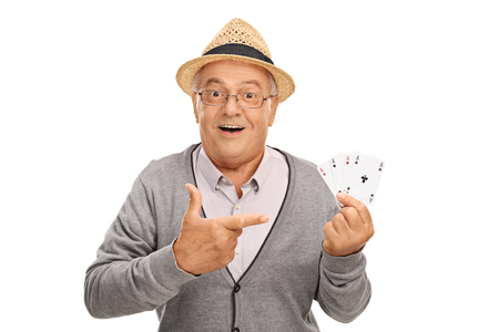 hand pointing: Senior man holding four aces in one hand and pointing at them with his other isolated on white background Stock Photo