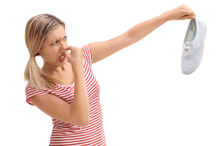 disgusted: Disgusted blond woman holding a stinky shoe isolated on white background Stock Photo