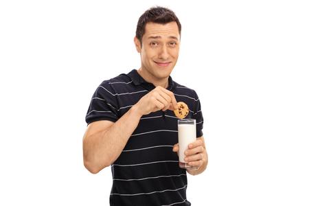 hombre comiendo: hombre joven que sumerge una galleta en un vaso de leche aislado en el fondo blanco