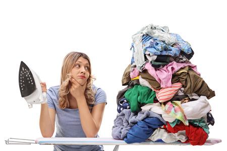 mujeres tristes: Sad joven explotación plancha y mirando a un gran montón de ropa aislado en el fondo blanco