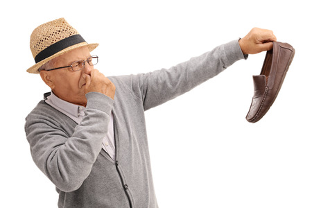 disgusted: Disgusted old man holding a smelly shoe isolated on white background