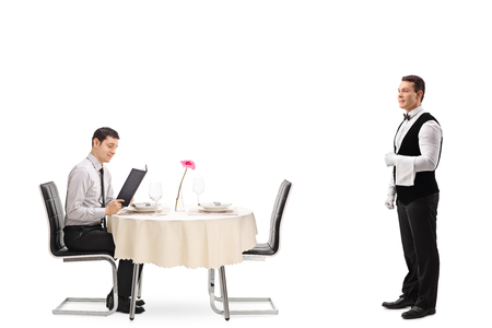 isolated man: Young man seated at a restaurant table reading a menu and a waiter waiting to be called isolated on white background