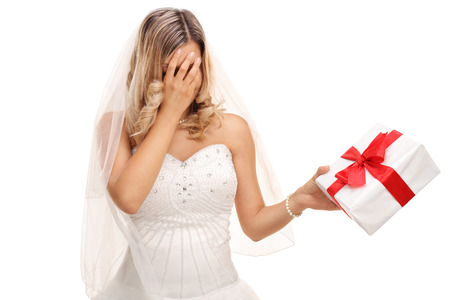 Young disappointed bride holding a wedding present in her hand isolated on white background Imagens