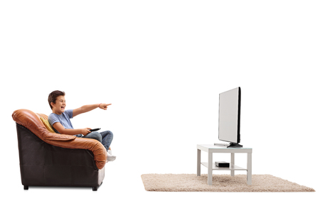 hilarious: Laughing child seated on an armchair watching something hilarious on tv isolated on white background