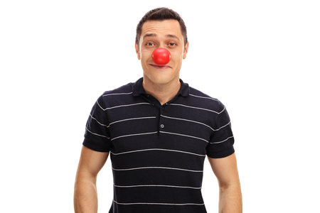 clown nose: Young guy posing with a red clown nose isolated on white background