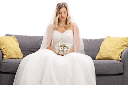 seated: Depressed bride seated on a sofa isolated on white background