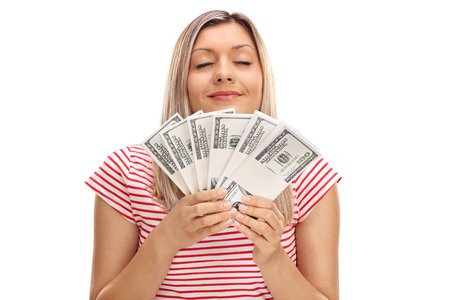 Young woman smelling stacks of money isolated on white background