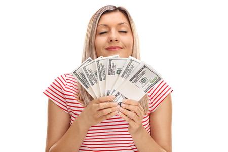 Jonge vrouw ruiken stapels van geld op een witte achtergrond