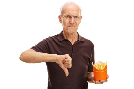 Senior man holding a bag of fries and making a thumb down gesture isolated on white background Stock Photo