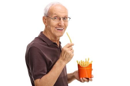 fry: Happy senior man eating fries isolated on white background
