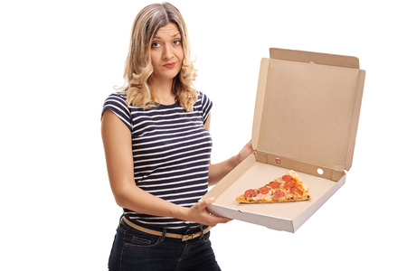 leftover: Disappointed woman holding a box with a single slice of pizza isolated on white background Stock Photo