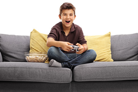 boys playing: Cheerful boy sitting on a sofa and playing video games isolated on white background