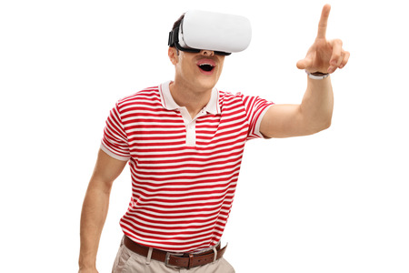 experiencing: Excited guy experiencing virtual reality and touching something with his finger isolated on white background Stock Photo