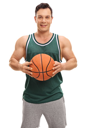 beginner: Smiling guy in a green jersey posing with a basketball isolated on white background