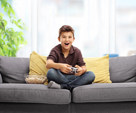 kids playing video games: Happy kid playing video games and sitting on a sofa