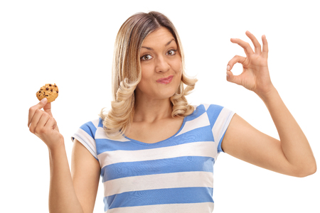 Cheerful woman eating a cookie and making an ok sign isolated on white background Stock fotó