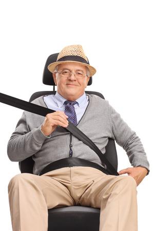 persona sentada: Hombre mayor sentado en un asiento de coche y sujetando el cinturón de seguridad aislado en el fondo blanco