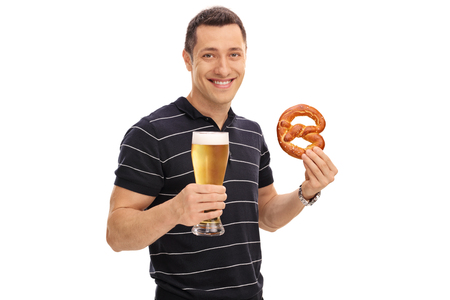 Happy man holding a pretzel and a pint of beer isolated on white background Stock Photo