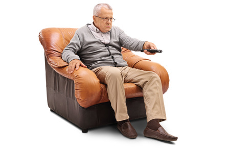 Angry senior sitting on an armchair and switching channels isolated on white background