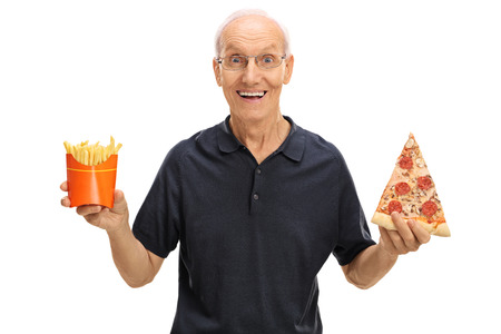 eating fast food: Cheerful elderly man holding a slice of pizza and fries isolated on white background Stock Photo