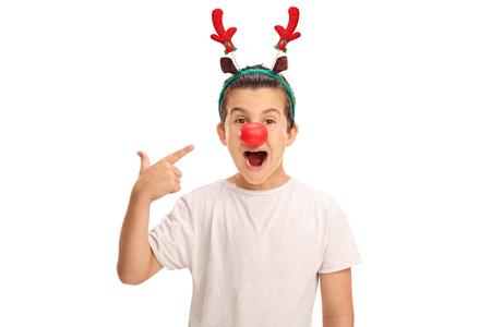 nariz roja: muchacho alegre que presenta con orejas de reno rojos y una nariz roja y apuntando a ellos aislado en el fondo blanco Foto de archivo