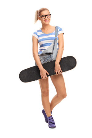 Skater girl posing with a skateboard isolated on white background