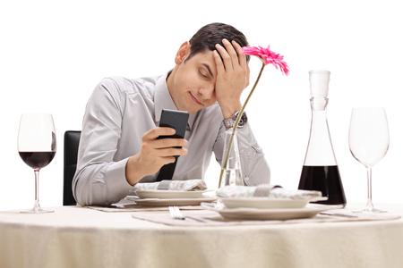 homme triste: Jeune homme lisant un message sur son téléphone et tenant sa tête dans l'incrédulité isolé sur fond blanc