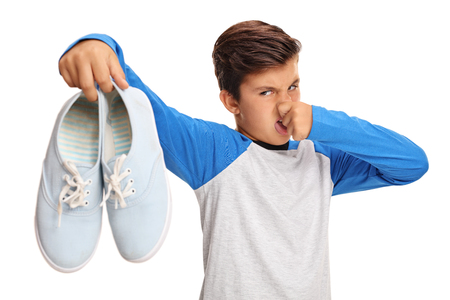 Disgusted boy holding a pair of smelly shoes isolated on white background