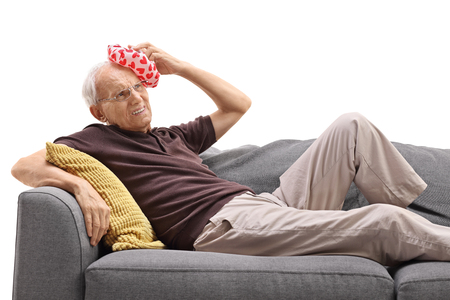 70s: Senior man lying on a sofa and having a headache isolated on white background Stock Photo
