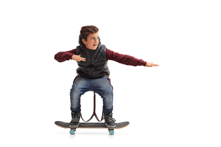 Cheerful boy riding a skateboard isolated on white background