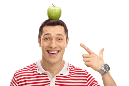 hand pointing: Happy guy pointing at an apple on his head isolated on white background Stock Photo