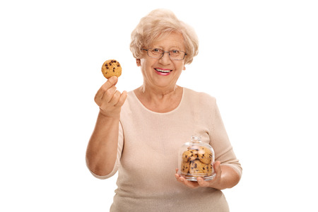 senior woman: Happy mature woman holding a cookie and a jar full of cookies isolated on white background