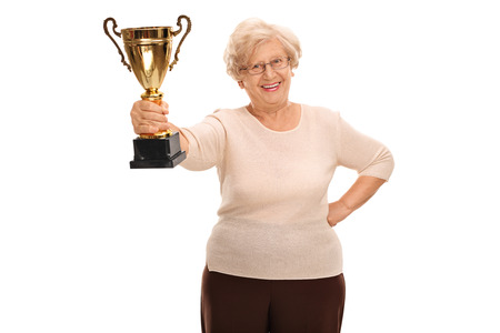 Cheerful elderly woman holding a golden trophy isolated on white background