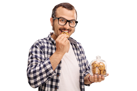 Smiling man eating a cookie and holding a jar full of cookies isolated on white background Stockfoto