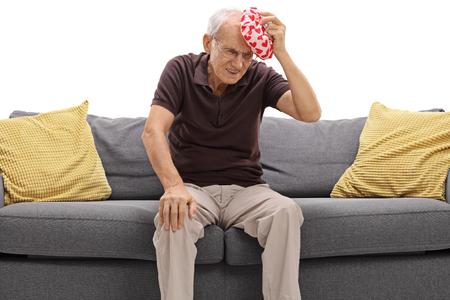 El hombre mayor que tiene un dolor de cabeza y la celebración de una bolsa de hielo aislados sobre fondo blanco