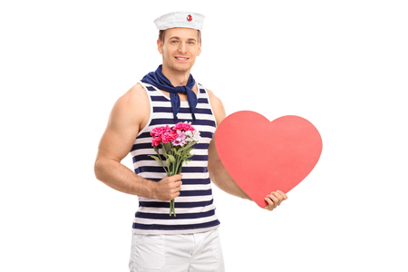 Handsome sailor holding a bouquet of flowers and a heart isolated on white background photo