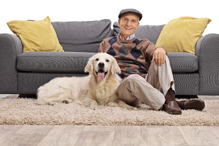 Mature man and his dog posing together on the floor isolated on white background