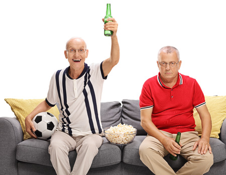 white men: Two mature men watching football and cheering for a different team isolated on white background
