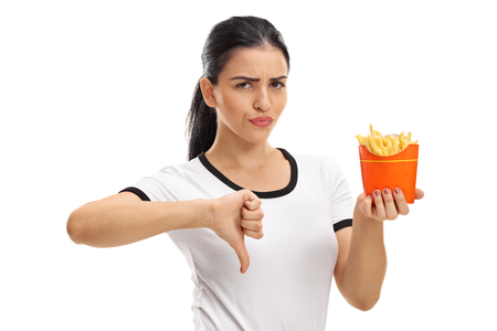 Young woman holding a bag of fries and making a thumb down gesture isolated on white background Stock Photo
