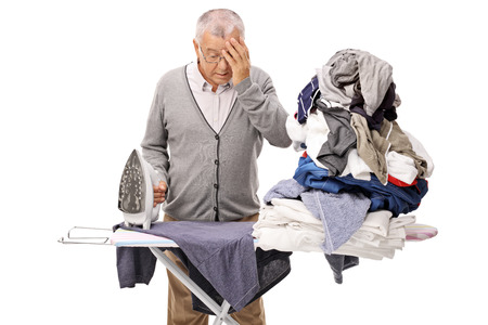 Mature man ironing and holding his head in disbelief isolated on white background