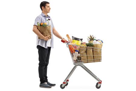 carretilla de mano: Retrato de cuerpo entero de un hombre esperando en la cola con un carrito de compras y una bolsa de papel aislado en el fondo blanco Foto de archivo