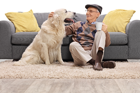 petting: Mature man sitting on the floor and petting his dog isolated on white background