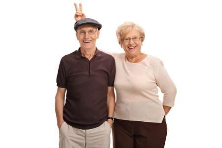 Ältere Frau, die ihren Mann mit Hasenohren auf weißem Hintergrund pranking