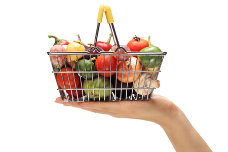 Close-up of a hand holding a small shopping basket full of vegetables and fruits isolated on white background