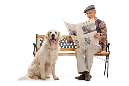 70s: Elderly man sitting on a bench wth his dog and reading a newspaper isolated on white background.