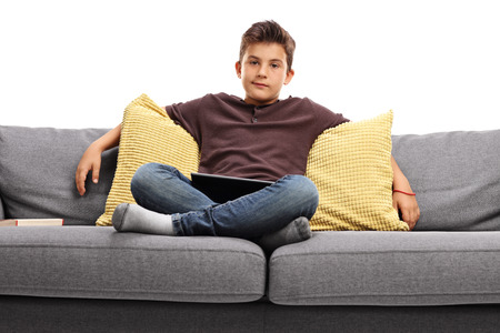 disinterested: Bored boy sitting on a sofa isolated on white background