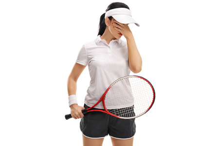 disbelief: Disappointed female tennis player holding her head in disbelief isolated on white background Stock Photo