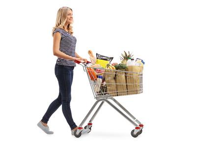 empujando: Retrato de cuerpo entero de una mujer joven que empuja un carro de compras llena de comestibles aisladas sobre fondo blanco Foto de archivo