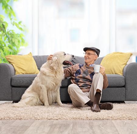 Uomo anziano seduto sul pavimento e accarezzare il suo cane